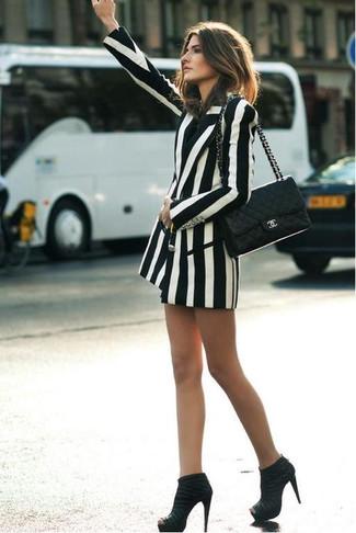 Cómo combinar: bolso de hombre de cuero acolchado negro, botines de ante negros, blazer cruzado de rayas verticales en blanco y negro