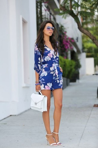 Cómo combinar: gafas de sol morado, bolso de hombre de cuero blanco, sandalias de tacón de cuero blancas, mono corto con print de flores azul