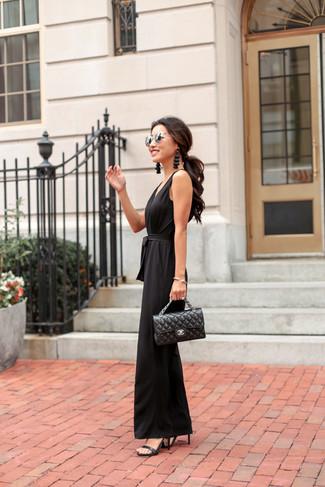 Cómo combinar: gafas de sol plateadas, bolso de hombre de cuero acolchado negro, sandalias de tacón de cuero negras, mono negro