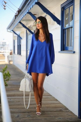 Cómo combinar: gafas de sol amarillas, bolso deportivo de cuero blanco, sandalias de tacón de cuero blancas, vestido amplio azul