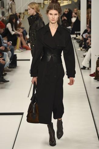 Cómo combinar: cinturón de cuero negro, bolso deportivo de cuero en marrón oscuro, botines de cuero en marrón oscuro, gabardina negra