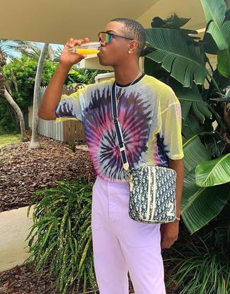 Cómo combinar: gafas de sol naranjas, bolso mensajero de lona estampado amarillo, pantalón chino violeta claro, camiseta con cuello circular efecto teñido anudado en multicolor