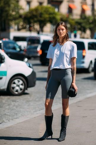 Cómo combinar: collar dorado, botas a media pierna de ante negras, mallas ciclistas en gris oscuro, camiseta con cuello circular blanca