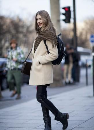 Cómo combinar: mochila de cuero negra, botas a media pierna de cuero negras, vaqueros pitillo de cuero negros, abrigo en beige