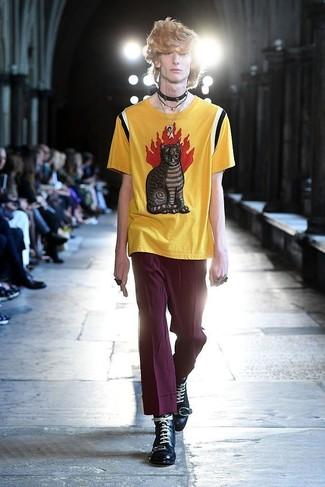 Combinar un pantalón chino morado: Ponte una camiseta con cuello circular estampada amarilla y un pantalón chino morado para lidiar sin esfuerzo con lo que sea que te traiga el día. Usa un par de botas casual de cuero negras para mostrar tu inteligencia sartorial.