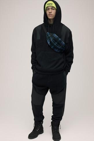 Cómo combinar: gorro en amarillo verdoso, botas casual de ante negras, pantalón de chándal negro, sudadera con capucha negra