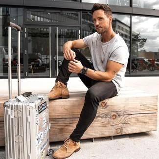 Cómo combinar: maleta plateada, botas casual de ante marrón claro, vaqueros pitillo negros, camiseta con cuello circular gris