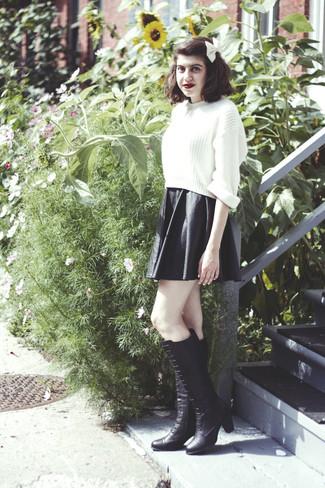 Cómo combinar: corbatín blanco, botas de caña alta de cuero negras, falda skater de cuero negra, jersey corto de punto blanco