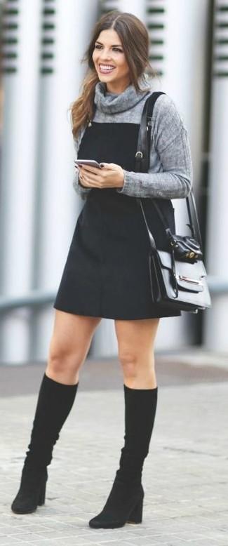 Cómo combinar: bolso bandolera de cuero negro, botas de caña alta de ante negras, pichi vaquero negro, jersey con cuello vuelto holgado gris
