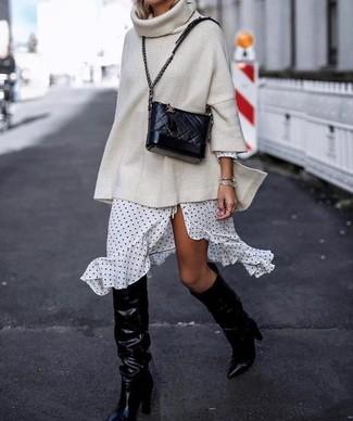 Cómo combinar: bolso bandolera de cuero acolchado negro, botas de caña alta de cuero negras, vestido cruzado a lunares en blanco y negro, jersey oversized de punto en beige