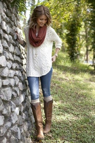 Cómo combinar: bufanda burdeos, botas de caña alta de cuero marrónes, vaqueros pitillo desgastados azules, jersey de ochos blanco