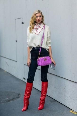 Cómo combinar: bolso bandolera de cuero morado, botas de caña alta de cuero rojas, vaqueros pitillo negros, jersey oversized gris