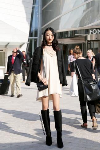Cómo combinar: bolso bandolera de cuero negro, botas de caña alta de ante negras, vestido amplio en beige, chaqueta de tweed negra