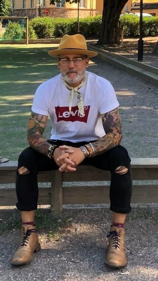 Cómo combinar: sombrero de lana marrón claro, botas formales de cuero marrón claro, vaqueros pitillo desgastados negros, camiseta con cuello circular estampada en blanco y rojo