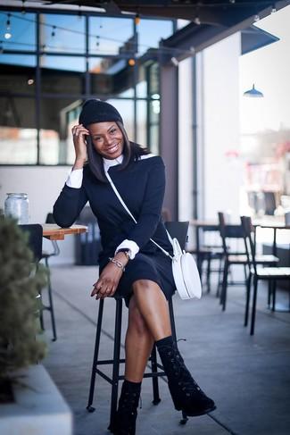 Cómo combinar: bolso bandolera de cuero blanco, botas planas con cordones de ante negras, camisa de vestir blanca, vestido con hombros al descubierto negro
