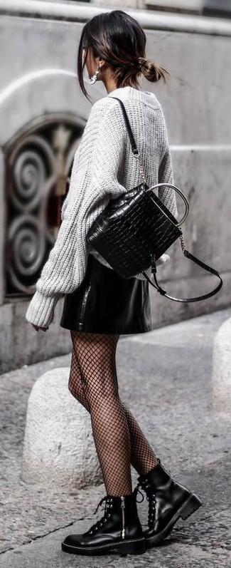Cómo combinar: mochila de cuero acolchada negra, botas planas con cordones de cuero negras, minifalda de cuero negra, jersey oversized de punto gris