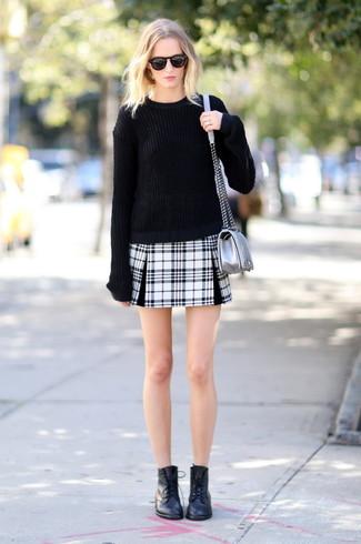 Cómo combinar: bolso bandolera de cuero plateado, botas planas con cordones de cuero negras, minifalda de tartán en negro y blanco, jersey oversized negro