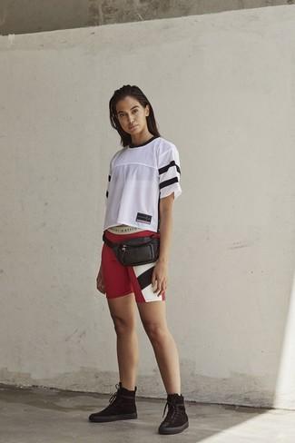 Cómo combinar: riñonera de cuero negra, botas planas con cordones de ante negras, mallas ciclistas estampadas rojas, camiseta con cuello circular de malla blanca