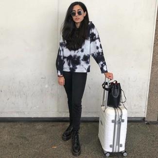 Cómo combinar: mochila con cordón de cuero negra, botas planas con cordones de cuero negras, vaqueros negros, sudadera efecto teñido anudado en negro y blanco