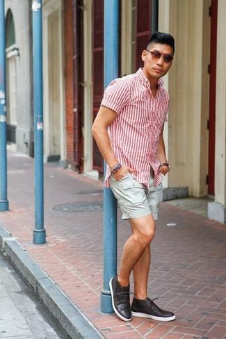Cómo combinar: gafas de sol marrónes, botas safari de cuero en marrón oscuro, pantalones cortos grises, camisa de manga corta de rayas verticales en blanco y rojo