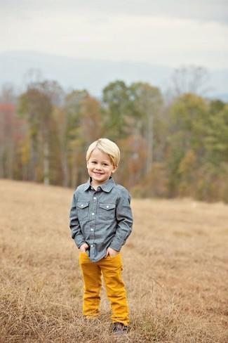Cómo combinar: botas safari en marrón oscuro, pantalones naranjas, camisa de manga larga de cambray azul