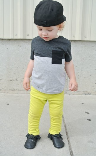 Cómo combinar: gorra de béisbol negra, botas safari negras, vaqueros en amarillo verdoso, camiseta gris