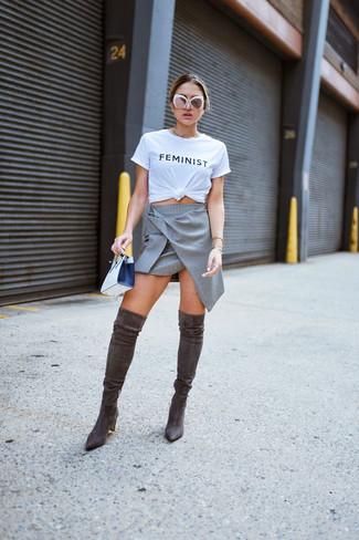 Cómo combinar: cartera sobre de cuero en blanco y negro, botas sobre la rodilla de ante en marrón oscuro, falda línea a gris, camiseta con cuello circular estampada en blanco y negro
