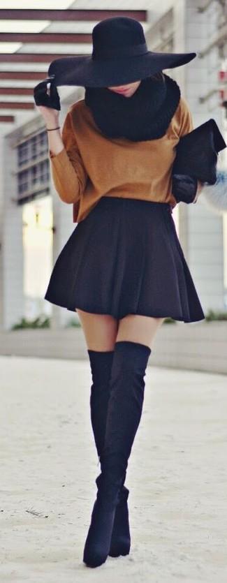Cómo combinar: cartera sobre de pelo negra, botas sobre la rodilla de ante negras, falda skater negra, jersey oversized en tabaco