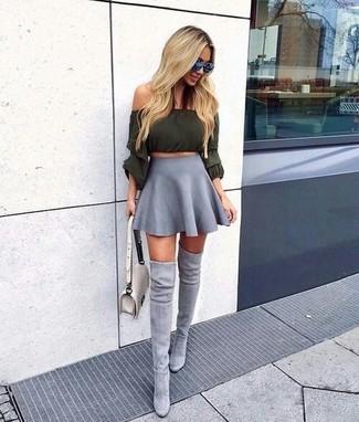 Cómo combinar: bolso bandolera de cuero acolchado en beige, botas sobre la rodilla de ante grises, falda skater gris, top con hombros descubiertos verde oliva