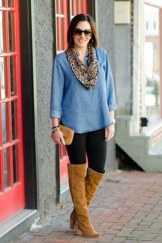 Cómo combinar: cartera sobre de cuero marrón claro, botas sobre la rodilla de ante marrón claro, leggings negros, túnica vaquera azul