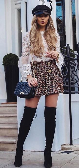 Una minifalda de vestir con unas botas sobre la rodilla de