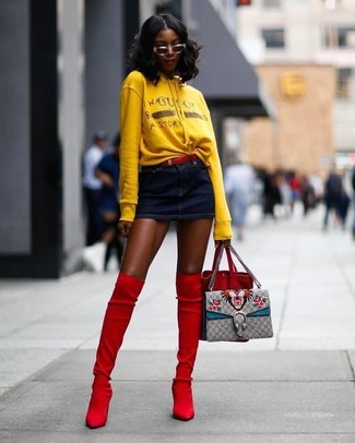 Cómo combinar: mochila con cordón de ante roja, botas sobre la rodilla de ante rojas, minifalda vaquera azul marino, sudadera con capucha estampada amarilla