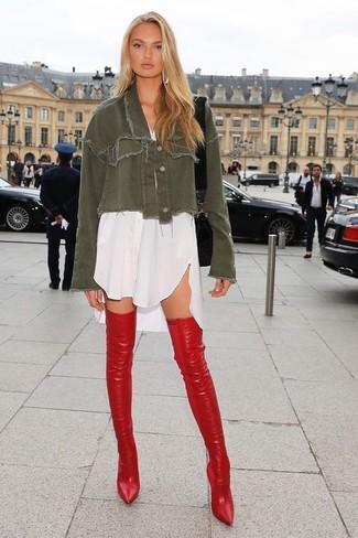 Cómo combinar: bolso bandolera de cuero negro, botas sobre la rodilla de cuero rojas, vestido camisa blanca, chaqueta vaquera verde oliva