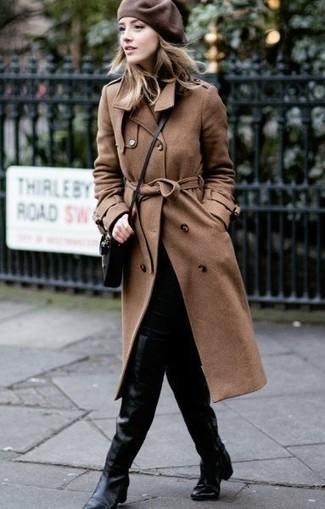 Cómo combinar: bolso bandolera de cuero negro, botas sobre la rodilla de cuero negras, vaqueros pitillo negros, gabardina marrón