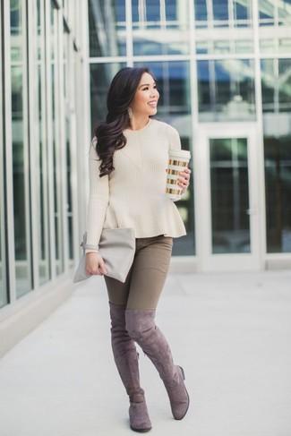 Cómo combinar: cartera sobre de cuero gris, botas sobre la rodilla de ante rosadas, vaqueros pitillo marrónes, jersey con cuello circular en beige