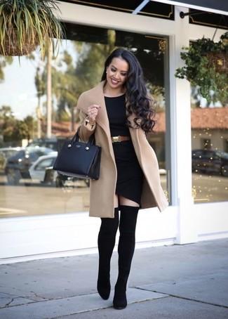 Cómo combinar: bolsa tote de cuero negra, botas sobre la rodilla de elástico negras, vestido ajustado negro, abrigo marrón claro