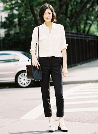 Cómo combinar: bolso bandolera de cuero negro, botines de cuero con recorte blancos, pantalones pitillo negros, camisa de vestir blanca