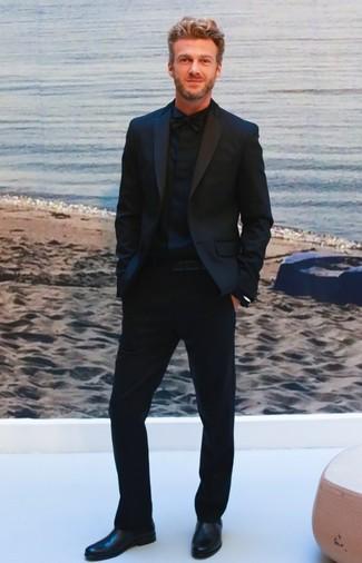 Cómo combinar: corbatín negro, botines chelsea de cuero negros, camisa de vestir negra, traje negro