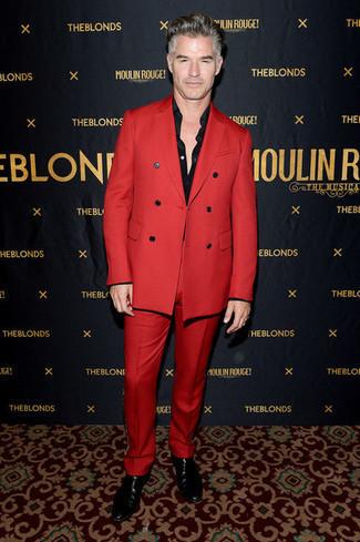 Outfits hombres: Usa un traje rojo y una camisa de vestir negra para una apariencia clásica y elegante. Para darle un toque relax a tu outfit utiliza botines chelsea de cuero negros.