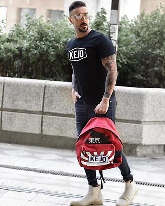 Cómo combinar: mochila estampada roja, botines chelsea de ante en beige, vaqueros pitillo en gris oscuro, camiseta con cuello circular estampada en negro y blanco