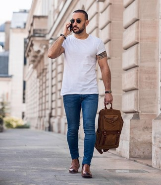 Cómo combinar: mochila marrón, botines chelsea de cuero marrónes, vaqueros pitillo azules, camiseta con cuello circular blanca