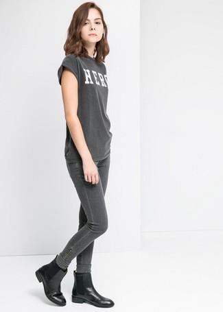 Cómo combinar: calcetines de lana en gris oscuro, botines chelsea de cuero negros, vaqueros pitillo en gris oscuro, camiseta con cuello circular estampada en gris oscuro