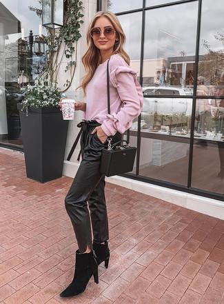 Cómo combinar: bolso bandolera de cuero negro, botines chelsea de ante negros, pantalón de pinzas de cuero negro, jersey con cuello circular rosado