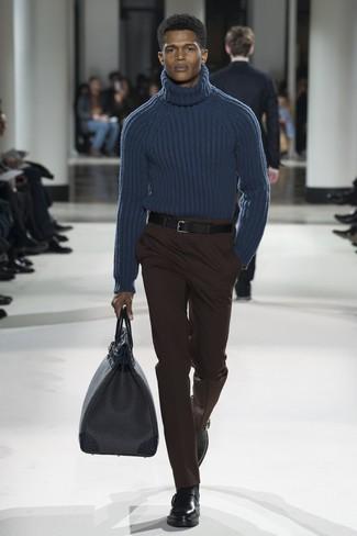 Cómo combinar: bolsa de viaje de cuero negra, botines chelsea de cuero negros, pantalón de vestir en marrón oscuro, jersey de cuello alto de lana de punto azul marino