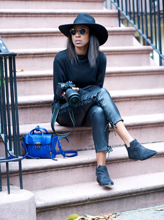 Cómo combinar: bolso bandolera de cuero azul, botines chelsea de ante negros, pantalones pitillo de cuero negros, sudadera negra