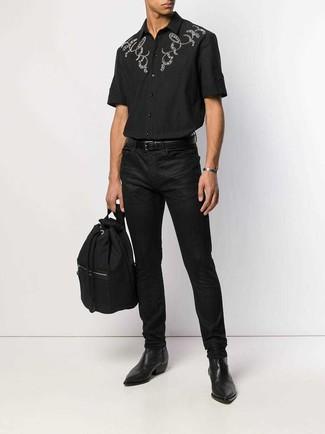 Cómo combinar: mochila de lona negra, botines chelsea de cuero negros, vaqueros negros, camisa de manga corta bordada negra