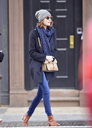 Cómo combinar: bolso bandolera de cuero en beige, botines chelsea de cuero marrónes, vaqueros pitillo azules, abrigo azul marino