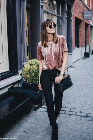 Cómo combinar: bolso bandolera de cuero negro, botines chelsea de ante negros, vaqueros pitillo negros, camiseta con cuello circular de terciopelo rosada