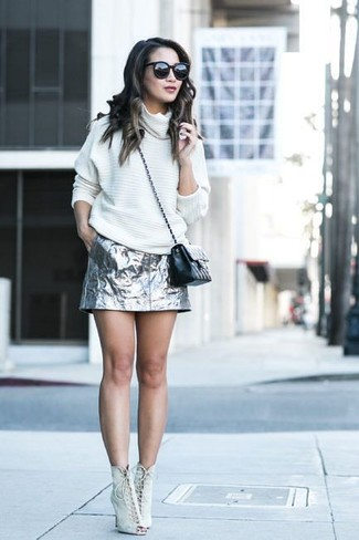 Cómo combinar: bolso bandolera de cuero acolchado negro, botines con cordones de ante en beige, minifalda plateada, jersey oversized blanco