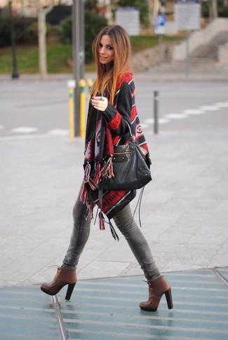 Cómo combinar: bolsa tote de cuero negra, botines con cordones de cuero marrónes, vaqueros pitillo grises, poncho estampado negro